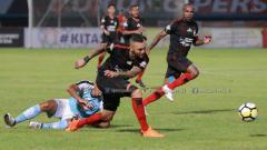 Indosport - Marcel Sacramento menendang bola (kiri) dan Boaz Solossa (kanan).