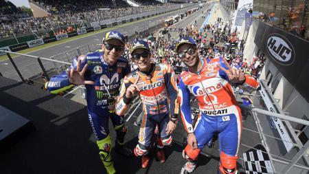 Marc Marquez bersama Danilo Petrucci dan Valentino Rossi berdiri di podium. - INDOSPORT