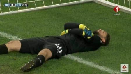 Kiper Timnas Tunisia, Mouez Hassen tertangkap kamera berpura-pura cedera demi berbuka puasa di laga uji coba melawan Turki, Sabtu (02/06/18). - INDOSPORT