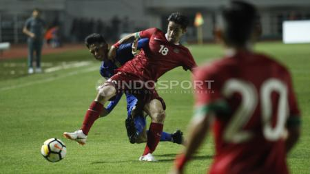 Perebutan bola antara Gavin Kwan dengan pemain Thailand. - INDOSPORT
