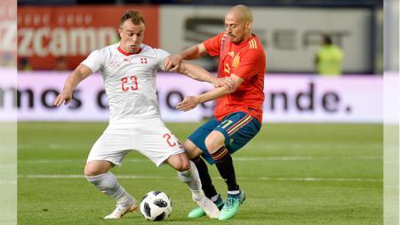 Perebutan bola antara Shaqiri (kiri) dengan Iniesta (kanan). - INDOSPORT