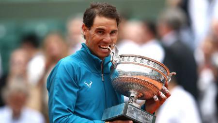 Rafael Nadal memegang trofi Roland Garros. - INDOSPORT