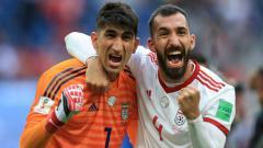 Indosport - Kiper Iran Alireza Beiranvand dan Rouzbeh Cheshmi selebrasi usai kalahkan Maroko di laga Grup B Piala Dunia 2018.