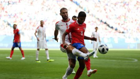 Johan Venegas mendapat tekel dari Branislav Ivanovic di pertandingan Piala Dunia 2018 yang mempertemukan Kosta Rika dengan Serbia. - INDOSPORT