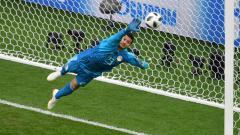 Indosport - Kiper Mesir, Mohamed El-Shenawy, saat menepis tendangan pemain Uruguay, Edinson Cavani dalam laga Piala Dunia 2018.