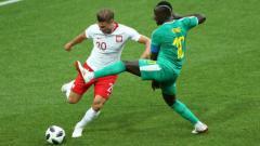 Indosport - Bek Polandia Lukasz Piszczek berusaha membuang bola dan dihalau pemain Senegal Sadio Mane di Piala Dunia 2018.