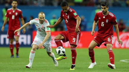 Peamin Iran mendapat bola namun berusaha direbut Iniesta. - INDOSPORT