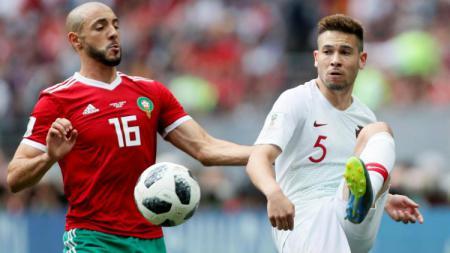 Pemain Maroko Nordin Amrabat dan Pemain Portugal Raphael Guerreiro berduel di Piala Dunia 2018. - INDOSPORT