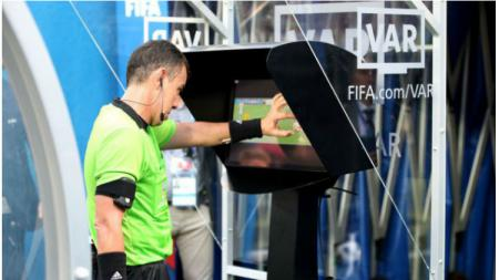 Wasit melihat Video Assistant Referee (VAR) di sisi lapangan. - INDOSPORT