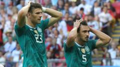 Indosport - Ekspresi kekecewaan Mats Hummels (kanan) dan Mario Gomez usai kekalahan Jerman dari Korea Selatan.