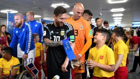 Kapten Argentina, Lionel Messi, berbicara dengan bocah maskot pertandingan di dalam lorong stadion jelang laga perdana Grup D Piala Dunia 2018 menghadapi Islandia. - INDOSPORT