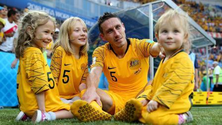 Bek Timnas Australia, Mark Milligan, sedang bercengkrama bersama putri-putrinya tercinta di tepi lapangan.