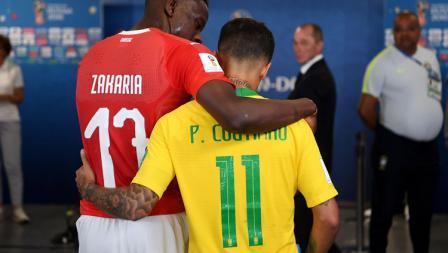 Bintang Brasil, Philippe Coutinho, berangkulan dengan pemain Swiss, Denis Zakaria.