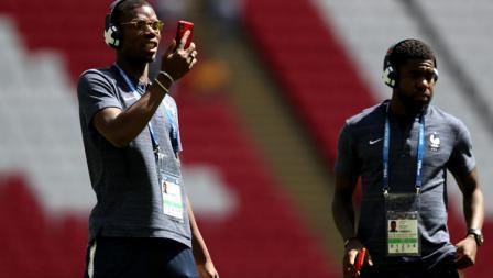 Gelandang Prancis, Paul Pogba, mencek smartphone-nya jelang laga perdana menghadapi Australia di Kazan Arena.