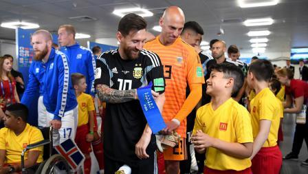Megabintang Argentina, Lionel Messi, berbincang dengan maskot cilik di lorong stadion jelang laga perdana melawan Islandia.