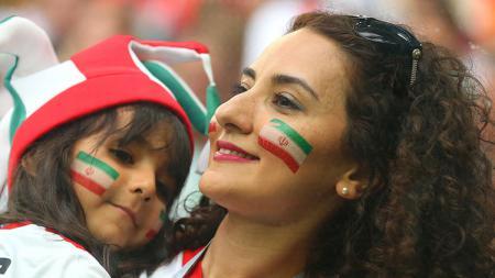 Ibu satu anak ini tidak mau ketinggalan untuk menyaksikan laga Iran vs melawan Spanyol dengan membawa anaknya. - INDOSPORT