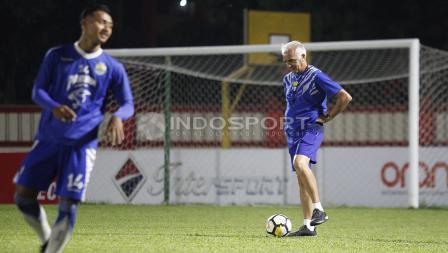 Pelatih Mario Gomez berkali-kali memperhatikan kondisi rumput stadion PTIK.