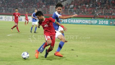 Asnawi Mangkualam duel dengan pemain Singapura U-19 untuk mendapatkan bola.