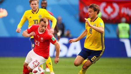 Xherdan Shaqiri berusaha melewati dua pemain Swedia sambil membawa bola. - INDOSPORT