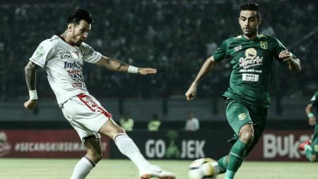 Adu Stefano Lilipaly dengan Otavio Dutra dalam laga Persebaya vs Bali United. - INDOSPORT