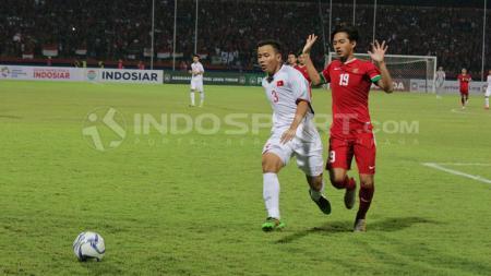Hanis Saghara berebut bola dengan Nguyen Hung Thien. - INDOSPORT