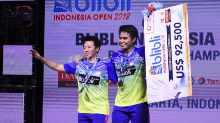 Ganda Campuran Indonesia Tontowi Ahmad dan Liliyana Natsir membawa poster hadiah sebagai juara Indonesia Open 2018. - INDOSPORT