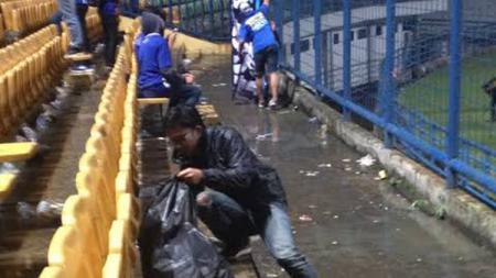 Bobotoh memunguti sampah selepas pertandingan Persib Bandung. - INDOSPORT