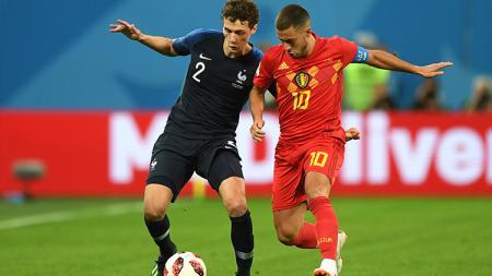Eden Hazard mencoba merebut bola di kaki Benjamin Pavard. - INDOSPORT