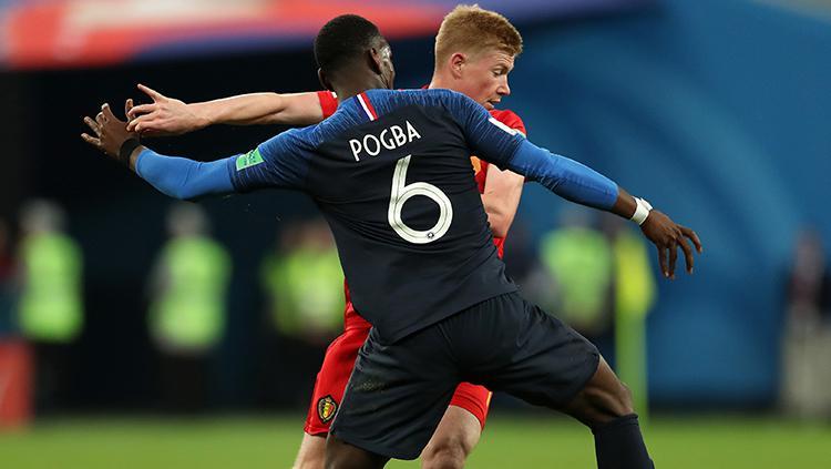 Paul Pogba mencoba merebut penguasaan bola dari De Bruyne. Copyright: INDOSPORT