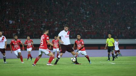 Wiljan Pluim berada dalam penjagaan pemain Bali United. - INDOSPORT