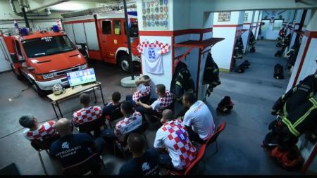 Petugas kebakaran asyik nonton laga Kroasia vs Rusia. - INDOSPORT
