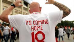 Indosport - Fans Inggris menggunakan baju bertuliskan It's Coming Home.