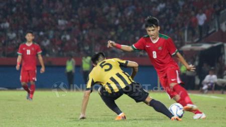 Witan Sulaiman memalingkan bola dari serangan pemain Malaysia. - INDOSPORT