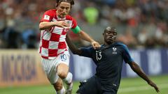 Indosport - N'GOlo Kante mencoba merebut penguasaan bola dari kaki Luka Modric.