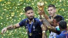 Indosport - Ekspresi bahagia Olivier Giroud usai berhasil meraih trofi Piala Dunia 2018.