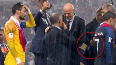 Wanita yang terekam kamera memasukan medali Piala Dunia ke dalam sakunya. - INDOSPORT
