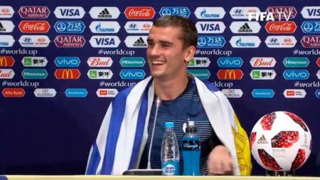 Antoine Griezmann mengenakan bendera Uruguay dalam konferensi pers pasca pertandingan final Piala Dunia 2018. - INDOSPORT