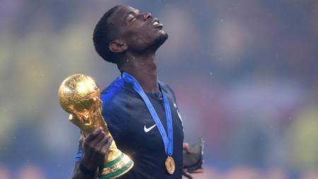 Paul Pogba bersama trofi Piala Dunia 2018. - INDOSPORT
