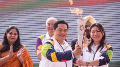 Indosport - Erick Thohir dan Susi Susanti membawa api obor di India.