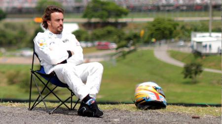 Fernando Alonso, pembalap F1 sedang duduk santai di pinggir Sirkuit Yas Marina, Abu Dhabi. - INDOSPORT