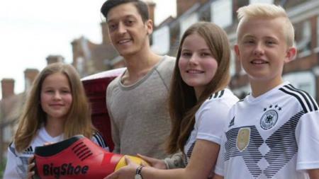 Mesut Ozil bersama anak-anak yang dibantunya dalam kegiatan amal - INDOSPORT
