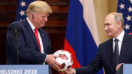 Usai gelar Piala Dunia 2018, Presiden Rusia, Vladimir Putin (kanan) berikan sebuah bola ke Presiden Amerika Serikat, Donald Trump. - INDOSPORT