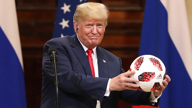 Presiden Amerika Serikat, Donald Trump memamerkan bola Piala Dunia 2018 yang diberikan Presiden Rusia, Vladimir Putin. Copyright: INDOSPORT