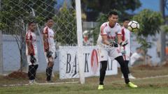 Indosport - Shahar Ginanjar saat mengamankan bola yang mengarah ke gawangnya.