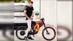 Indosport - Gerard Pique saat mengantar anaknya menggunakan sepeda.