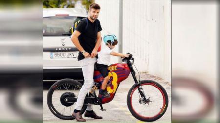 Gerard Pique saat mengantar anaknya menggunakan sepeda. - INDOSPORT