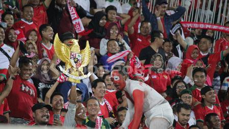 Suporter Indonesia, Andi Kiswantoro, membawa patung Garuda Pancasila. - INDOSPORT