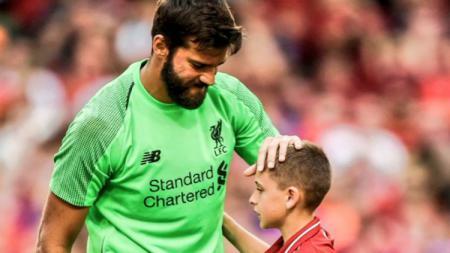 Aksi berkelas Alisson Becker kepada bocah fans Liverpool yang masuk ke lapangan. - INDOSPORT