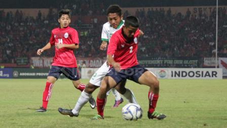 Muhammad Fajar (tengah) dikawal ketat dua pemain Kamboja.