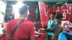 Indosport - Sejumlah pedagang jersey Timnas Indonesia di sekitaran Stadion Gelora Delta Sidoarjo, jelang babak semifinal Piala AFF U-16 2018.